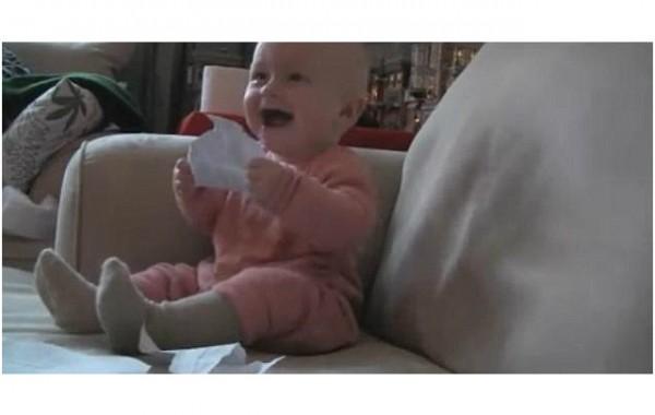Baby lacht om papier scheuren