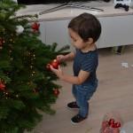 kind samen gezin kerstboom optuigen versieren